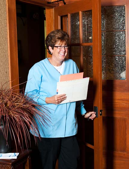 Deb the Patient Care Specialist comes through the waiting room door with a big smile to call a patient in for their dental appointment.