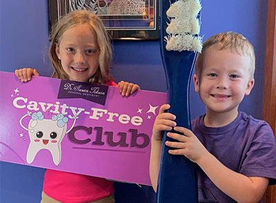 A smiling young brother and sister proudly display the Cavity Free Club sign after a successful dental visit.