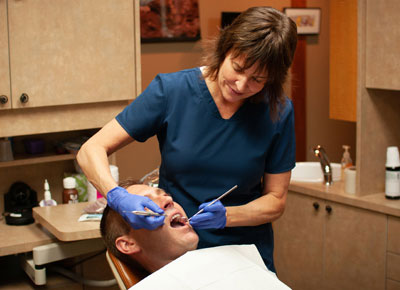 Link to the Adult Dentistry page showing Dr Tikson working on a male patient's teeth.
