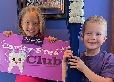 Link the the Pediatric Dentistry page showing a young brother and sister proudly holding the Cavity Free Club sign after their dental visit.
