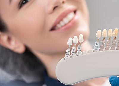 Link to the Cosmetic Dentistry page showing a young woman choosing the right color for her teeth veneers.