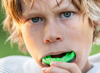 Link to the Mouthguards page showing a young junior high football player taking out his sturdy green mouthguard.