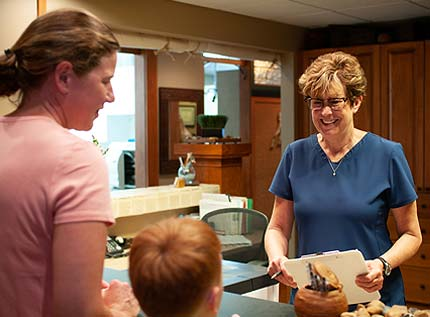 Patient Care Specialist, Deb, greets a young boy and his mother as they arrive for a dental appointment.