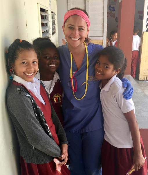 A smiling Dr Eichenlaub hugs three happy young girl patients in school uniforms during her dental mission trip to the Dominican Republic.
