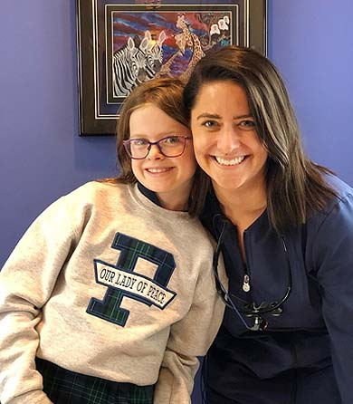 Dentist Audrey Eichenlaub posed next to a smiling young girl dental patient.