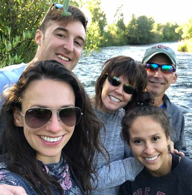Dr Susan Tikson relaxing by a riverbank with her husband and three adult children during a summer vacation.