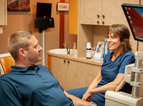 Dentist Susan Tikson smiles and talks to a male patient in a relaxed setting during his initial dental visit.