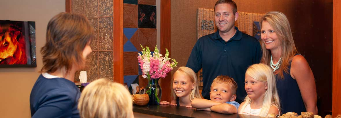 Dentist Susan Tikson greets a family with three young children at the front desk as they arrive for their dental appointment.