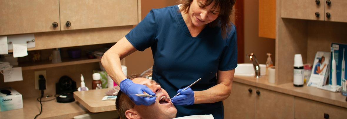 Dentist Susan Tikson gently examines a male dental patients teeth.