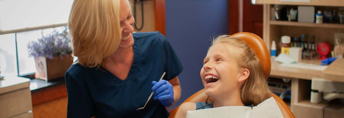 Smiling female dental hygienist laughing with a young girl dental patient putting her at ease during a teeth cleaning.