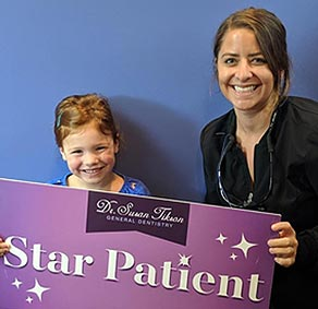 Dr Eichenlaub helps a smiling little girl patient proudly hold up the Star Patient sign after her great dental visit.