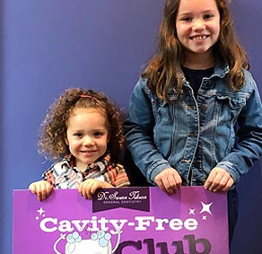 Two young sisters proudly hold up the Cavity Free Club sign after their successful dental visits.