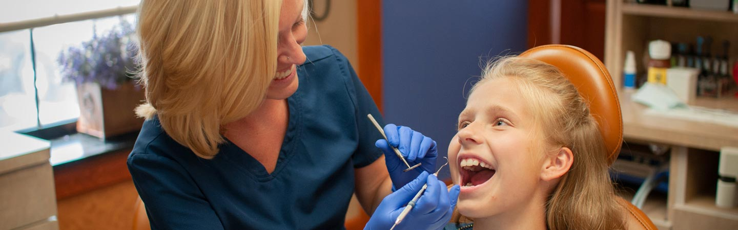 Smiling female dental hygienist puts a young girl at ease during a teeth cleaning.