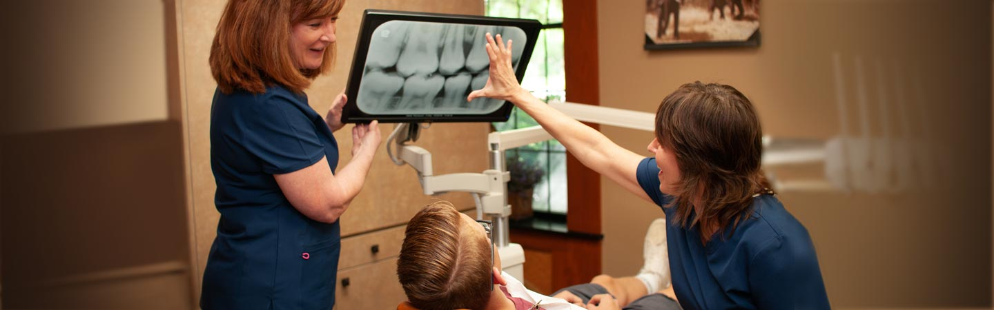 Dentist Susan Tikson and a smiling dental hygienist show a teenage boy dental patient his teeth xrays.